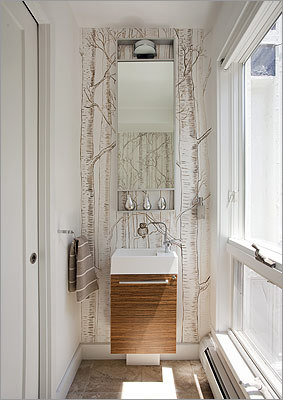 Go tall: A long, narrow mirror and small, sleek vanity keep the powder room feeling open, not cramped.