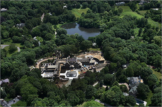 """A pond sits behind the Henry's home. The house has more than 35,000 square feet of living space. He is constructing a home theater, a theater lobby, a """"grotto,'' (very Plato's Retreat!), a two-tier garage for eight cars, a """"safe room,'' sports lounge, chef's kitchen, family kitchen, and """"her study'' for his wife, Linda Pizzuti. Read the full story"""