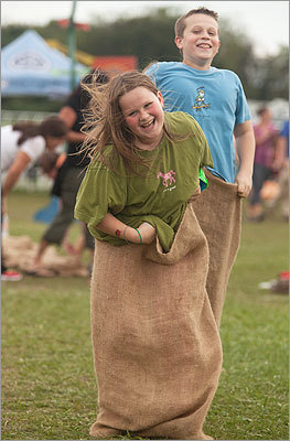 Anna, 10, and Billy, 12, both of Marshfield, during a potato sack race on the sidelines of the festival. Anna won the race, saying that she preferred the activities to the music. 'This is more fun,' she said.