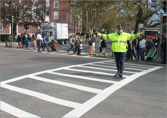 A Massachusetts State Police officer held up his hands to stop traffic for pedestrians along JFK Street. Behind him, barricades prevented traffic from turning onto Memorial Drive, which was closed for the Head of the Charles.