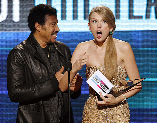 The 39th annual American Music Awards took place Sunday night at the Nokia Theater in Los Angeles. Check out scenes from the show or skip ahead for red carpet photos . Singer Taylor Swift said she didn't prepare an acceptance speech for the artist of the year award -- even though she's won it once before. Presenter Lionel Richie (left), no stranger to the AMAs, stood nearby. Swift won three awards this year.