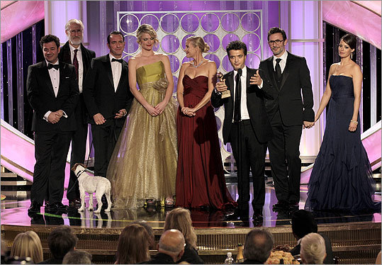 Thomas Langmann (at microphone) and the cast and crew of 'The Artist' celebrated the award for best motion picture, comedy or musical. From left: Ludovic Bource, James Cromwell, Uggie the dog, Jean Dujardin, Missy Pyle, Penelope Ann Miller, Michel Hazanavicius, and Bernice Bejo.