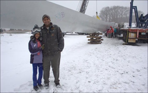 Sumul Shah, the CEO of Solaya Energy and the owner of the turbine, stands with his daughter, Solaya Shah, at the signing.