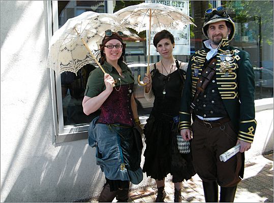 "Loo Catalano, 28, Kristin Boucher, 29, and Eric Catalano, 38, posed under lacey parasols to protect themselves from the sun. Loo and Eric married in October, adopting a steampunk theme for the wedding that took place at the Commander's Mansion in Watertown. ""I turned to come down the aisle, and I saw all these top hats and I was just so excited for it,"" Loo said."
