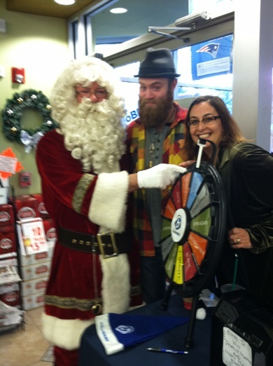 Santa spins the prize wheel with RadioBDC Street teamer Russell Caldwell and Julie Kramer