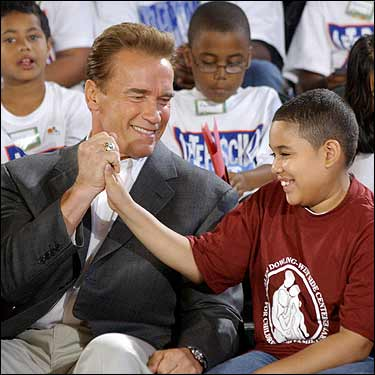 Arnold Schwarzenegger high-fives Jonathon Espino, 12, during a visit to Public School 129 in Harlem today. While speaking at the Republican National Convention last night, the Governor of California pledged his continued support for after-school programs.