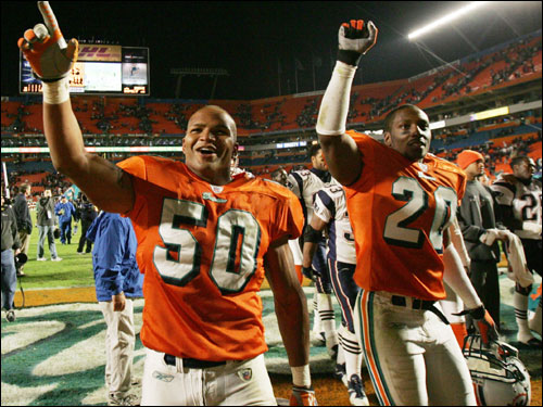 Arturo Freeman (right) and Brendon Ayanbadego (left) celebrate the Dolphins' unlikely 29-28 upset victory over the Patriots last night.