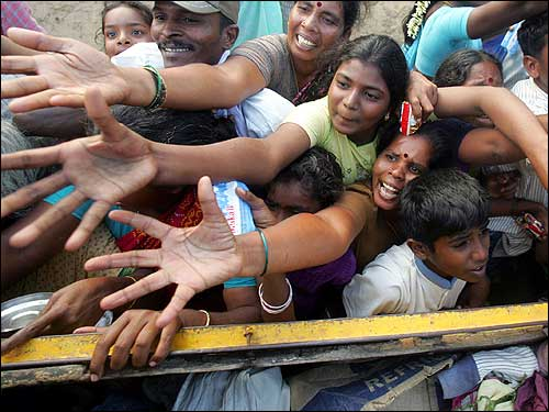 Tsunami survivors rush for clothes and food donated by volunteer organizations in Cuddalore, about 112 miles south of Madras.