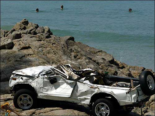 Tourists take a swim in front of a wreck of a car stuck on rocks on Phaton Beach in Phuke.