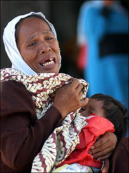 An Indonesian woman weeps as she holds a child. The UN children's agency UNICEF said about a third of the victims were likely to be children, as children make up at least a third of the population in the 10 countries most touched by the disaster.