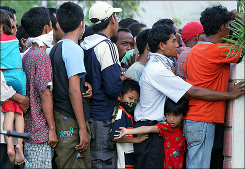 Indonesians line up for food in Banda Aceh. Military ships and planes rushed to get desperately needed aid to Sumatra's ravaged coast.