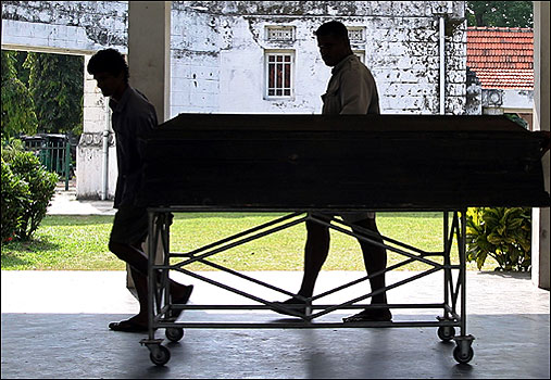 Workers in Colombo pull a gurney carrying the coffin of an Italian tsunami victim.