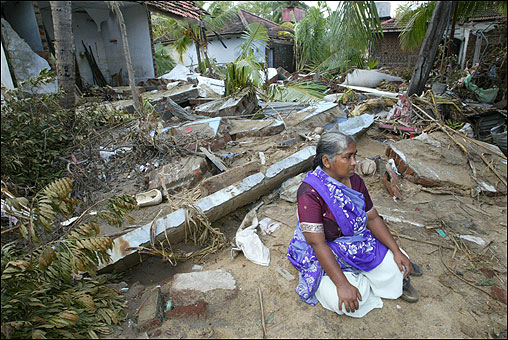 A woman sits in front of her destroyed house in Kalmuni.