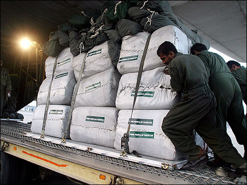 Pakistani porters load relief supplies prepared by their government into a plane at Chaklala Air base in Rawalpindi to be sent to the Maldives.