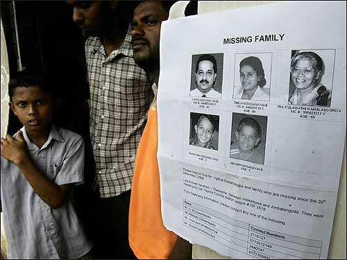 Homeless Sri Lankans stood next to a poster displaying pictures of missing compatriots in a refugee camp in Galagoda.