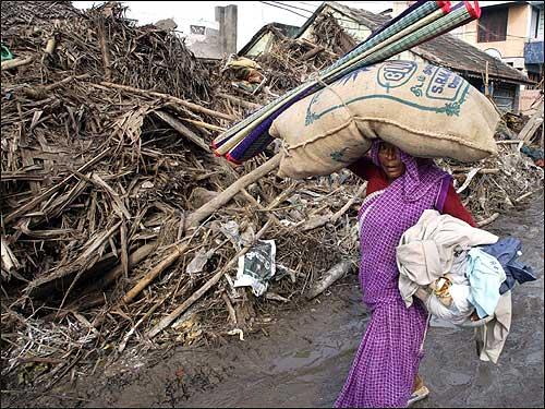A survivor carries her belongings as she returns to her village in Keechankuppam.