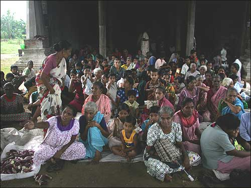 Women and children sit in a Hindu temple used temporarily as a refugee camp for tsunami survivors in the town of Kalmunai on Sri Lanka's east coast.