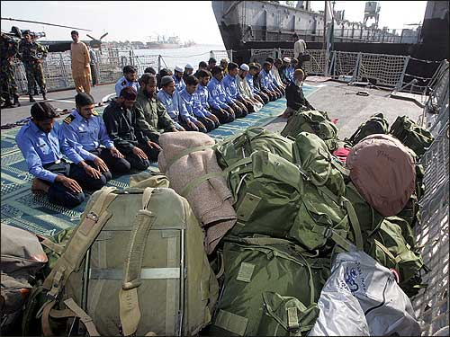 Pakistani soldiers pray onboard a ship at Karachi harbor, which is en route to tsunami-devastated areas in Asia.