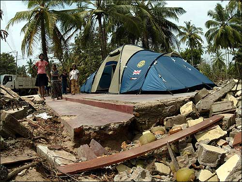 A tent offered by the Rotary Club of the United Kingdom is placed on a collapsed house. The tent will be used as a temporary refuge for a family of seven people near Galle, in southern Sri Lanka.
