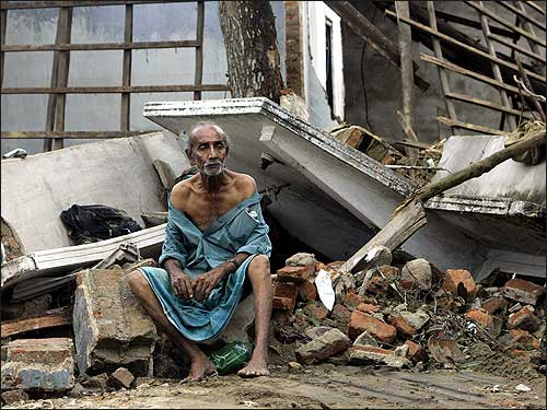 Sri Lankan Dalugoda Gilbert, 70, sits among the ruins of his home in the suburbs of Galle, in southern Sri Lanka.