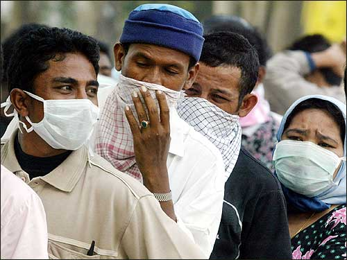 Acehnese residents use masks while lining up for clean water in Banda Aceh.