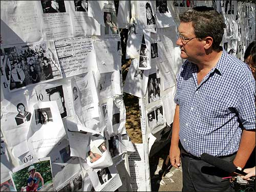 Australia's Foreign Minister Alexander Downer views some of the hundreds of missing persons photos on billboards at city hall on the Thai resort island of Phuket. Nearly 5,200 people, almost half of them foreign tourists, died when the devastating tsunami punched into the Thai coast. A further 3,800 are missing, including nearly 1,700 foreigners.