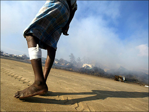 An Indian tsunami survivor looks at the debris of destroyed houses being burnt by Indian workers at a fishing hamlet in Nagapattinam, 219 miles south of the Indian city of Madras.