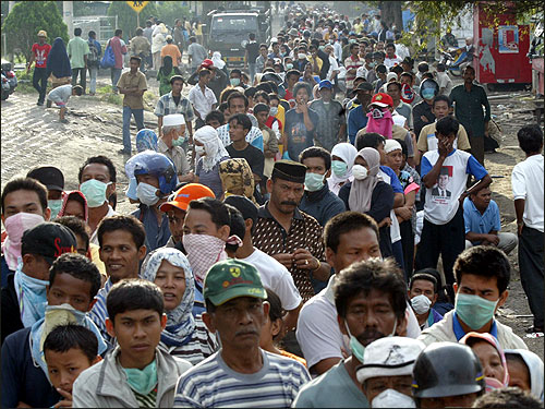 A line for supplies on a street in Banda Aceh extends into the distance.