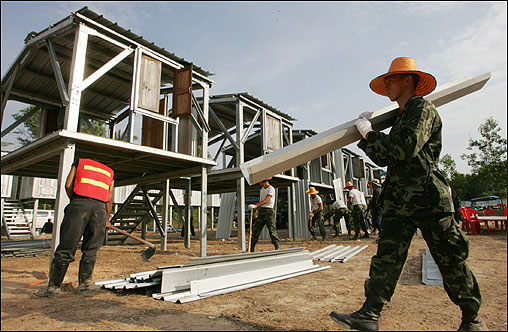 Soldiers help build temporary lodgings for Nam Khem villagers who lost their houses in the tsunami. Nam Khem is in the Takuapa district, about 81 miles north of Phuket Island.