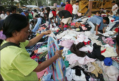 A woman from Nam Khem village chooses clothes from a donation pile today in the Takuapa district.