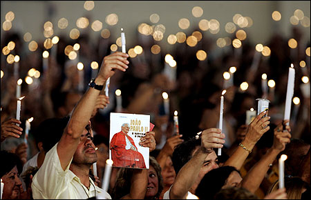 Worshipers in Sao Paulo held candles and an image of the pope yesterday at a special Mass said before his death.