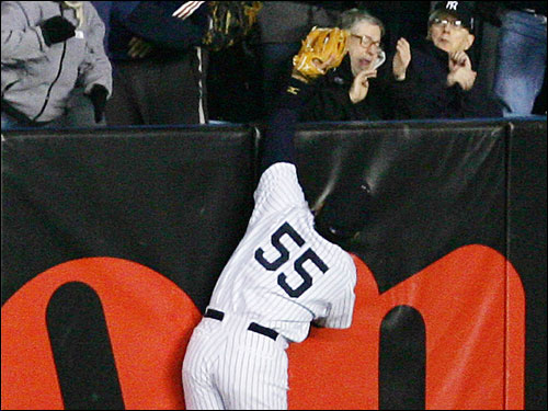 Yankees left fielder Hideki Matsui leaps and reaches into the stands to rob Red Sox first baseman Kevin Millar of a home run in the second inning.