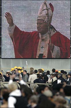 Mourners beneath a screen of the pope.