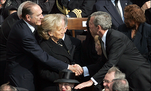 President George W. Bush leaned over to shake hands with French President Jacques Chirac and his wife Bernadette.