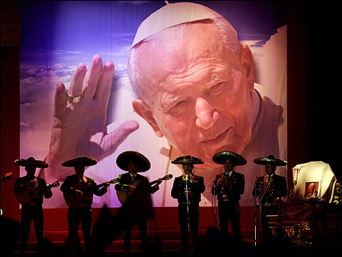 A mariachi band played at a televised tribute to Pope John Paul II as an empty chair stood to the right of the forecourt of the Basilica of Guadalupe in Mexico City.