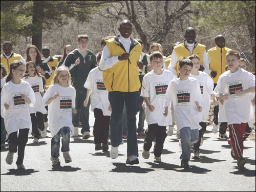 Kenyan marathoners run with Elmwood Elementary students yesterday in Hopkinton.