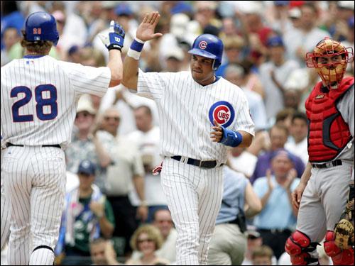 Cubs batter Aramis Ramirez congratulates teammate Todd Hollandsworth (28) as Red Sox catcher Jason Varitek looks away after Hollandsworth hits a two-run home run scoring Ramirez during the second inning.