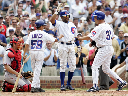 Chicago Cubs batter Greg Maddux is congratulated by a bat boy and teammate Neifi Perez as Red Sox catcher Jason Varitek looks on after Maddux hit a home run during the sixth inning.