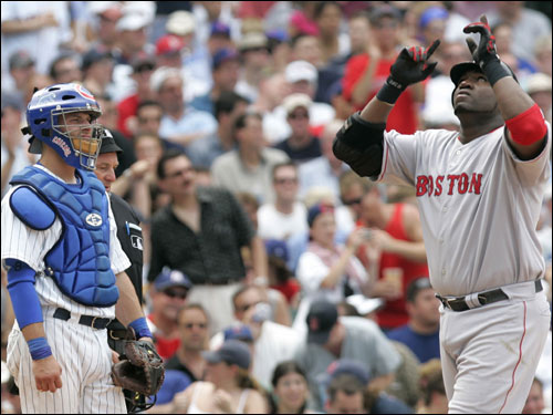 David Ortiz points skyward after hitting a solo home run as Cubs catcher Michael Barrett looks on during the sixth inning.