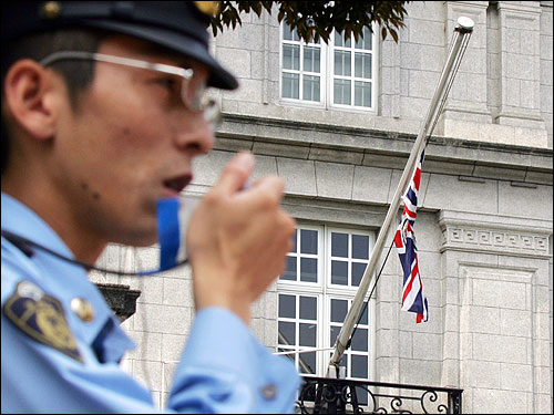 A Japanese policeman used a radio in front of the British Embassy in Tokyo today. The British flag hung at half-staff out of respect for those killed in the bombings yesterday. A nervous Japan, recalling its own deadly subway attack a decade ago, was on guard today.