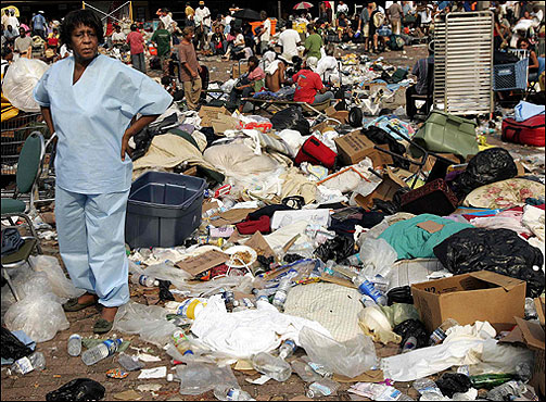 A woman stood among debris outside the Superdome as stranded people waited in lines to evacuate New Orleans.