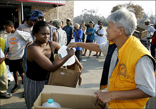 Ronnie Nguyen of the 'Supreme Master Ching Hai' religious organization handed water to residents of Biloxi, Miss., Saturday. The US military will send home from Iraq and Afghanistan more than 300 Air Force airmen based in Mississippi to allow them to assist their families.