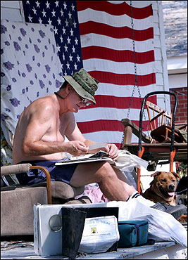 Vietnam veteran Mike Bass looked through his belongings for his Purple Heart medal and other memorabilia at his damaged home in Biloxi, Miss.