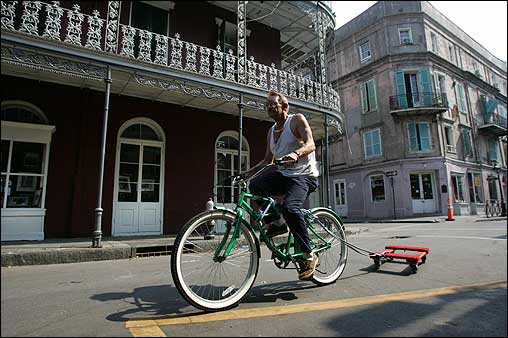 A man rode his bike on the streets of the French Quarter on Monday. Many residents of New Orleans who live in the few areas on high ground that escaped flood waters have said that they will defy official requests for them to evacuate.