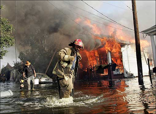 A New Orleans fireman helped evacuate a man out of flood waters as a home burned in the city's 7th Ward. The toxic brew of chemicals and human waste in the flood waters must be pumped into the Mississippi River or Lake Pontchartrain, raising the specter of an environmental disaster on the heels of Hurricane Katrina, experts say.