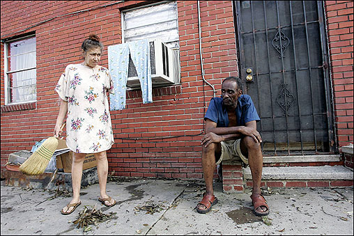 Hurricane Katrina holdout Anthony Gibson sat as Altair Gabel cleaned up outside their apartment in New Orleans.