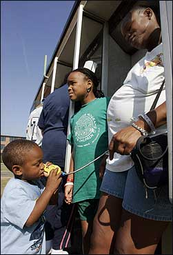 Jakam Bannister, 3, of New Orleans, talked on the telephone to a sister in Texas as his other sister, Nico Bannister, 8, (center) and their mother, Dionne White (right), stood nearby at Camp Edwards in Bourne.