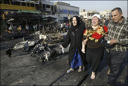 A woman cried as she walked with family members past the scene of bomb attacks at a bus station in Baghdad yesterday.
