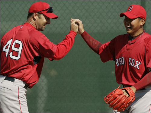 Red Sox pitcher Daisuke Matsuzaka (right) of Japan got a high five from teammate Tim Wakefield during practice at the team's spring training facility in Fort Myers on Tuesday.