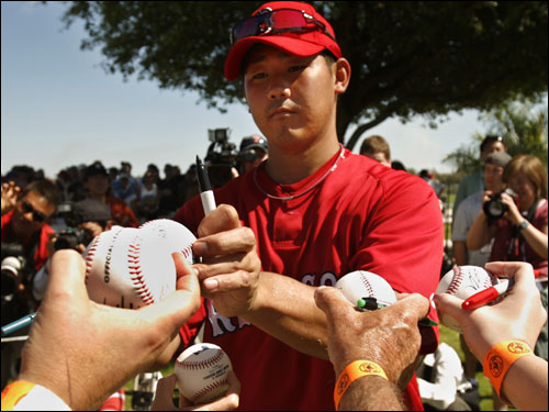 Daisuke Matsuzaka signs autographs for fans after practice Wednesday in Fort Myers.